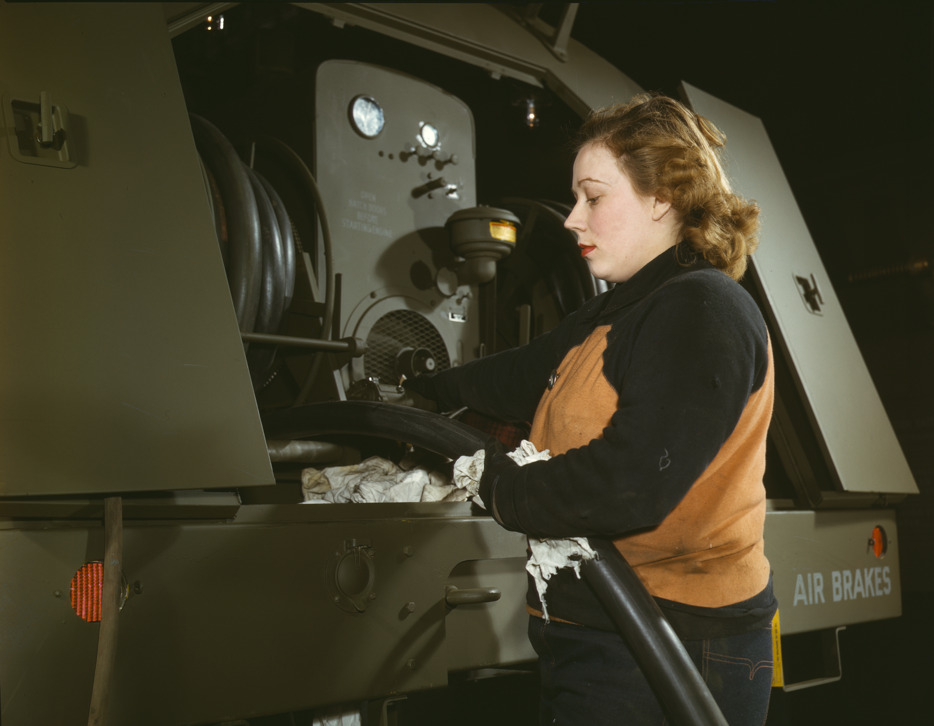Woman War Worker Checks Gasoline Trailer Hoses