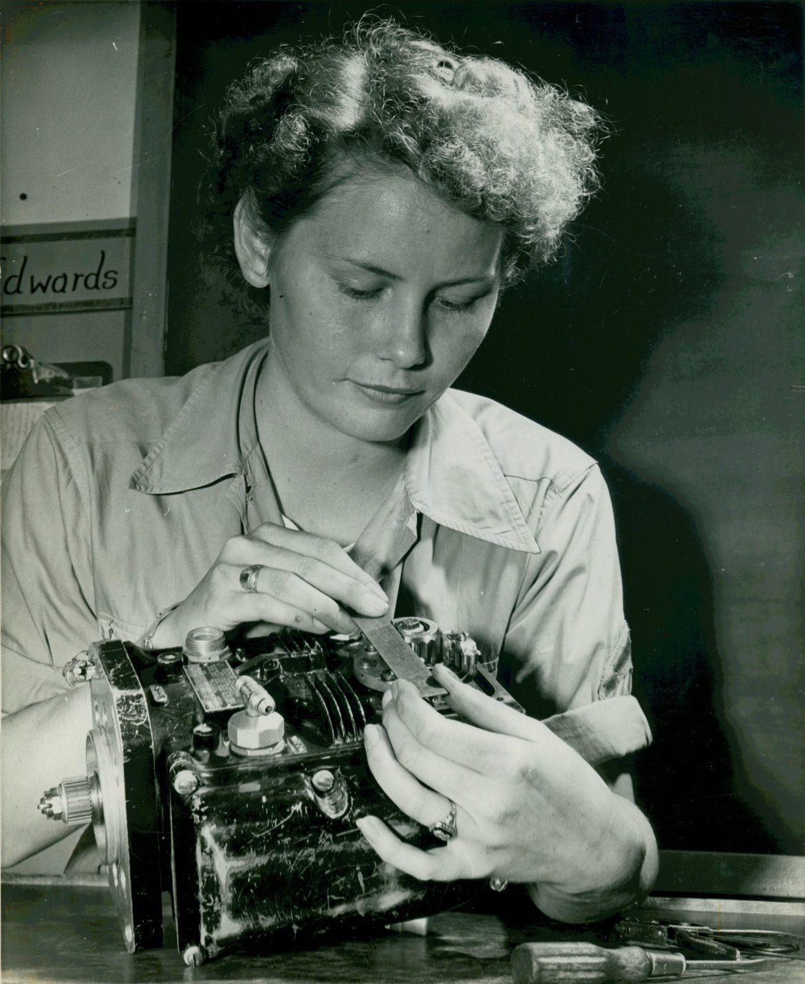 Woman Marine Works on Carburetor