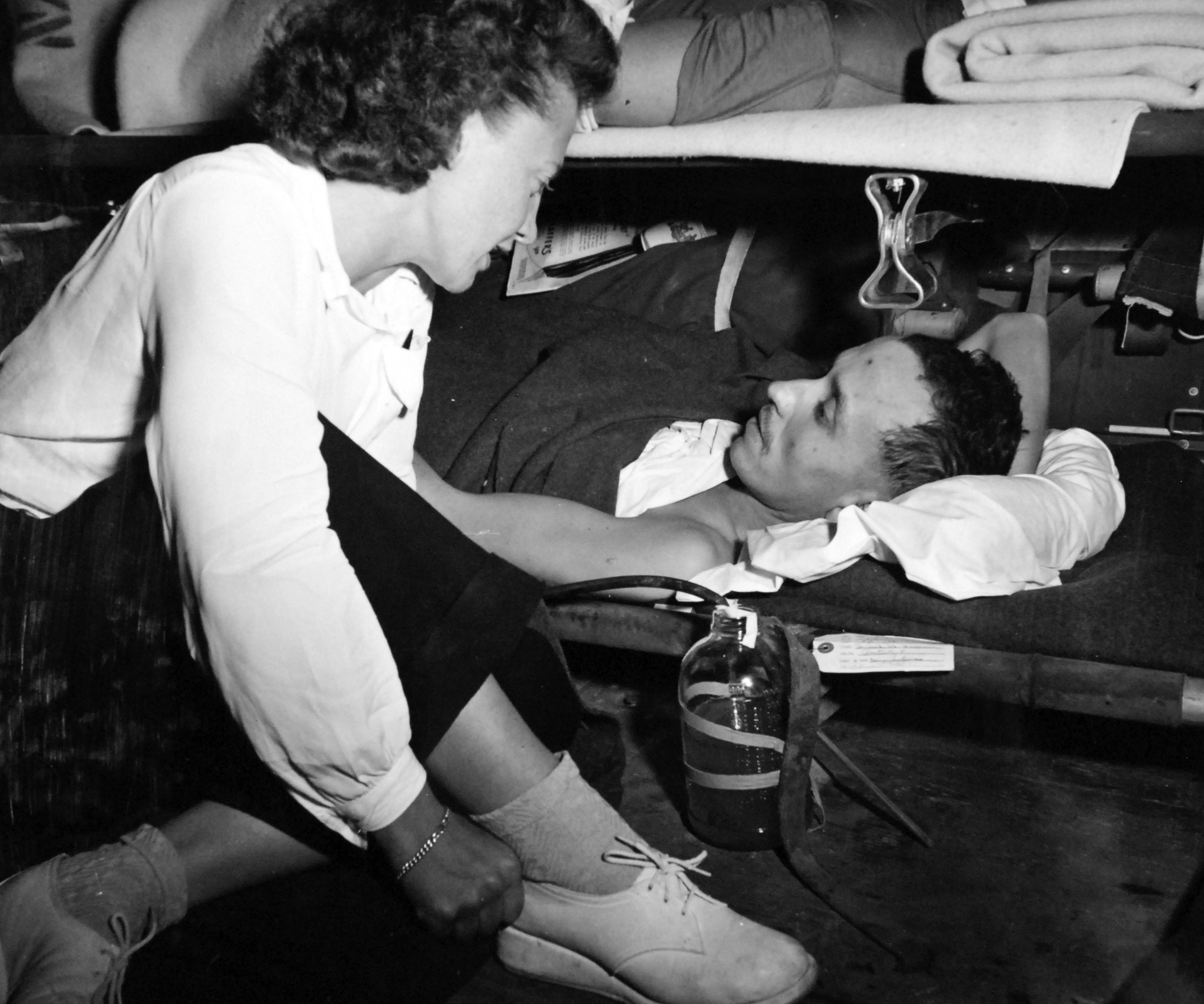 Navy Nurse Comforts Patient During Air Evacuation