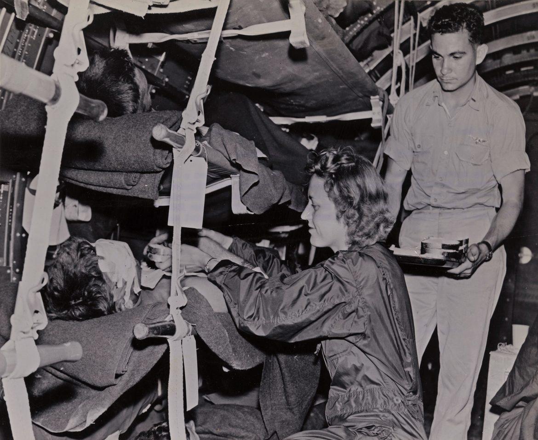 Navy Flight Nurse Feeds Wounded Evacuee