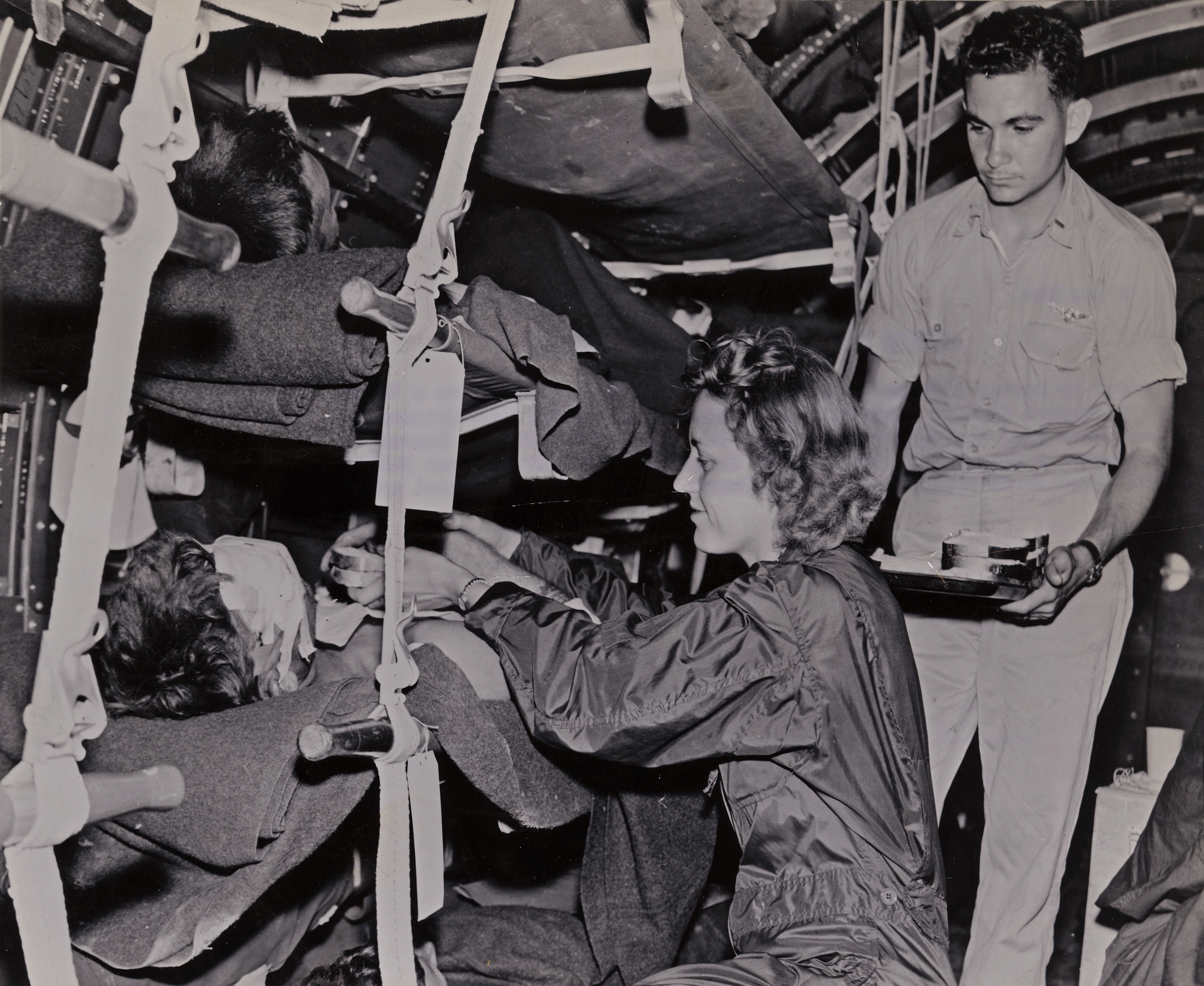 Navy Flight Nurse Feeds Wounded Evacuee
