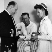 Navy Nurse Assists with Dressing Patient's Hand