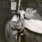 Navy Flight Nurse Jane Kendeigh Checks Patient Inflight