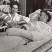 Navy Nurse Taping Cast of Wounded Sailor