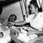 Nurse Opens Christmas Package for Patient Aboard Ship